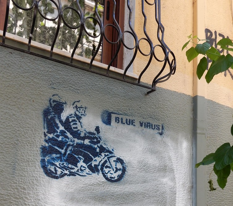 Graffiti of Greek Police on motorbike, blue virus