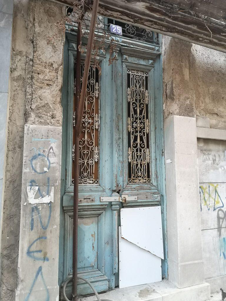 Crumbling blue door in Athens
